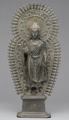 Standing Buddha with radiate combined halo, ca. late 6th century. Pakistan, ancient region of Gandhara. Brass