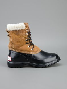 Black rubber snow boot from DSQUARED2 featuring a round toe, a corrugated rubber sole, a logo plaque at the rear of the heel, a brown sheepskin top section with contrast stitching, a shearling trim, an designer embossed plaque at the tongue and a front lace-up fastening.