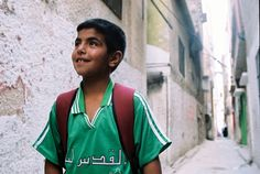 A young Palestinian boy returning home from a nearby school at Ein Beit Alma Refugee camp, the West Bank