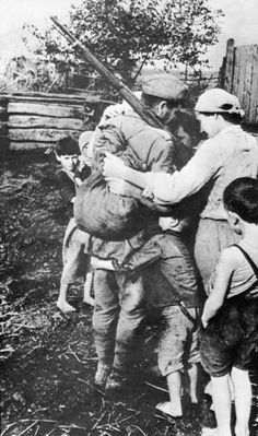 A Soviet soldier embracing his family after a long separation.