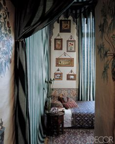 ElleDecor tented bedroom... bohemian and beckoning.  The guest room of Dimonah and Mehmet Iksel is tented with a striped Indian fabric, the bed is dressed with a Pakistani sari and pillows covered in 19th-century Azerbaijani weavings, and the printed Moghul panel is by Iksel.
