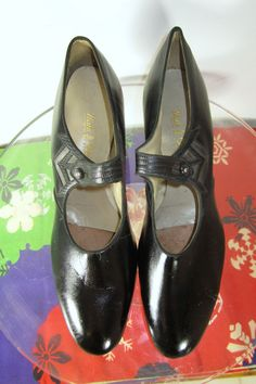 Vintage late 20s to early 30s Walkover brand black leather one strap pumps or walking shoes. They feature stacked leather heels and reptile embossing on the geometric Deco accents and straps, which fasten with pearly grey buttons.