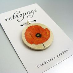 Take a page from our stylebookwith this unique pendant from retropage.Crafted from a vintage image ofa vibrant poppy,this accessory was handmade with love using the decoupage technique.