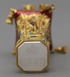 Gilt bronze, enamel, onyx 6.4 x 3.0 x 2.7 cm Seal surmounted by a gilt bronze spaniel standing on a guilloché enamel tassled cushion. The body cast and enamelled with exotic birds, squirrels and flowers. Onyx matrix. Royal Collection Her Majesty Queen Elizabeth II