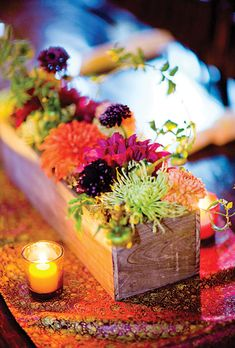 The centerpieces were wooden boxes filled with vibrant chrysanthemums and dahlias. All wedding flowers were by Peony & Plum Floral Design.