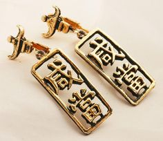 Pretty Gold Tone or plated Dangle Earring with Chinese Characters in a rectanglethat dangles freely from a roof top shape piece. The earrings are Vintage... The condition is good.  There is some...