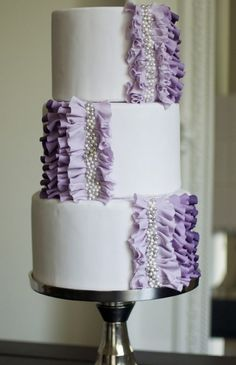 White wedding cake with purple ombre ruffles and amazing silver pearl detail!