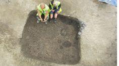 Två arkeologer sitter på kanten till ett grophus.