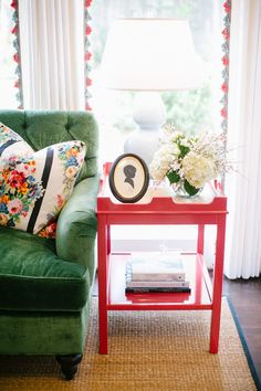 green velvet tufted sectional, red lacquer side tables, curtain trim Design by Bailey McCarthy photo by Kimberly Chau