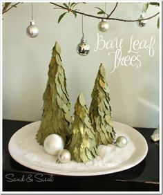 To make Bay Leaf Trees all you need is:  one large container of dried bay leaves (big box is $3 mol @ Sam's Club)  Aleen's Tacky Line Roll  paper mache cones or poster board formed into cones.  Start at bottom and overlap leaves, working around the tree.  A little Epsom salt poured in a plate makes snow for the trees to stand in.  These are rustic and smell nice, could leave them out all year.