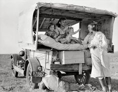 """August 1936. """"Family between Dallas and Austin. The people have left their home and connections in South Texas, and hope to reach the Arkansas Delta for work in the cotton fields. Penniless people. No food and three gallons of gas in the tank. The father is trying to repair a tire. Three children. Father says, 'It's tough but life's tough anyway you take it.'"""