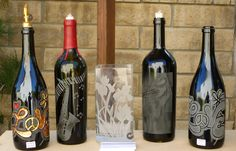 Re-purposed wine bottle designs transform into oil lamps as well as olive oil dispensers.  ( From left to right );  Love Design with gold leafing and red paint,  Graphic saxophone, with key board and floating notes, Jazz trumpet player, Standard love design.