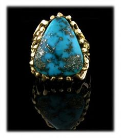 Morenci Turquoise Mens Gold Ring created by John Hartman of Durango Silver Company. John hand cut this wonderful high grade Morenci Turquoise gemstone from the Durango Silver Company American Turquoise Collection. It is an outstanding Turquoise gemstone that has iron pyrite matrix.  The Morenci gemstone is set in a spectacular lost wax masterpiece men's ring. Follow the source link to view additional photos of this great one of a kind piece of Turquoise Jewelry from the American Southwest.