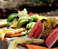 Fresh fruits and tropical flowers line the center of a wooden picnic table, serving as edible centerpieces!