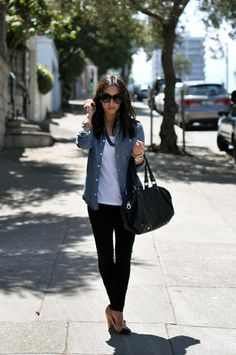 The blogger behind In the City with Crystalin takes a modern, polished, slightly edgy approach. She opts to wear her chambray button-down open, with a white tank underneath, pairing it with black skinnies, and nude and black spectator pumps. In addition, she wears big, black sunglasses, a black handbag, black necklace, and an assortment of bracelets.
