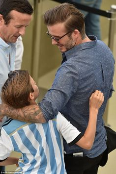Daddy's boy: David looks lovingly at son Cruz in his Argentina football shirt