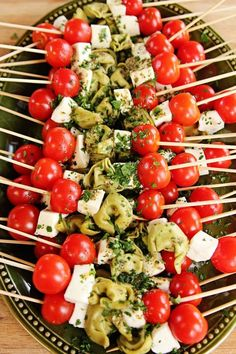 Pioneer womans Christmas red white and green appetizers of cherry tomatoes,fresh mozzarella,  and festive green tortellini. ... soo yummy!