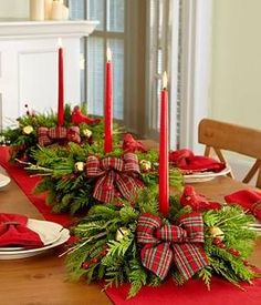 Pretty festive ribbon tied candles nested in pine tree clippings & holly...on red runner!