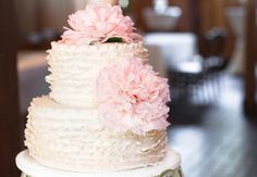White ruffled wedding cake, with pink flowers // Photo Love Photography