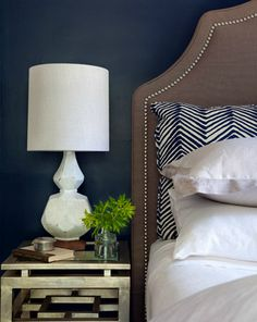 Stunning bedroom with navy blue walls paint color West Elm Terracotta Table Lamp, antique mirrored nightstand, brown linen headboard with nailhead trim and Quadrille Fabrics Alan Campbell Zig Zag Navy on Tint Fabric shams