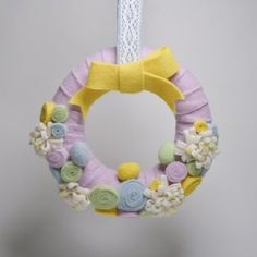 "Get in on the crafty felted décor trend with our sweet felted 15"" Easter Wreath! Wrapped in strips of soft pink felt, this spring wreath features pretty pastel rosettes, eggs and blooms to celebrate all things spring."