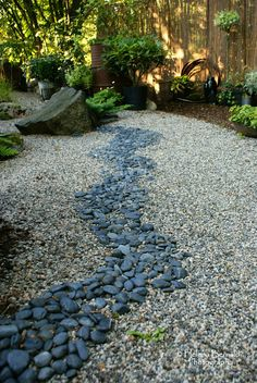 the line of dark rocks creates a very serene gravel garden/dry creek...I am going to be putting in a dry creek bed in my backyard at the end off my down spout where all of the mulch always washes away..I already have all of the rock to put in place.