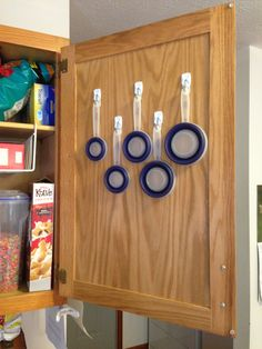 Hang small Command hooks up on the inside of a cabinet door and store measuring cups to give your drawers more room. These cups by SleekStor are collapsible, giving you even more space!