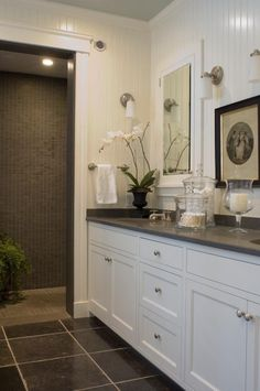 White vanity with dark tile and counter