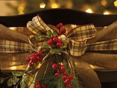 """""""Wrap the chair back with burlap. Wrap contrasting ribbon over the burlap and tie a bow. Stud with berries, greenery and a sled ornament."""""""