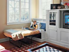 Family Room - Making Room for Guests - A built-in window seat flank each side of a children's entertainment unit in this light-filled upstairs family room. Each seat lifts up to reveal a twin sleeper pull-out bed. When not in use, the beds disappear inside the custom structures.