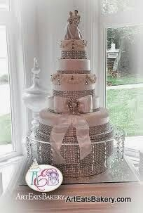 5 tier white elegant wedding cake design with rhinestones,  ribbons and bows,  brooch, and chandelier cake stand with Cinderella and Prince Charming topper