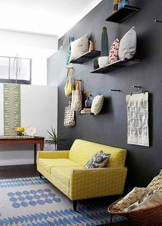 Love the dark wall and the color paired with the yellow couch. Also like the idea of displaying accessories!