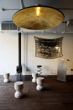 The giant pendant lamp is a satellite dish, plastered, painted, and covered in gold leaf.