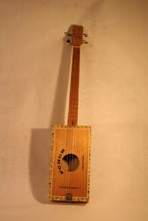 Punch tenor made out of a cigar box. The tallpiece is made out of an old fork.