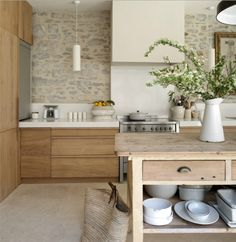 Modern kitchen with stone wall, from portfolio of interior designer Marie-Laure Helmkampf.