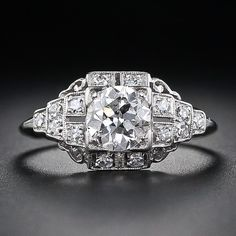 Art Deco .78 Carat Diamond Engagement Ring. This is a classic platinum Art Deco diamond engagement ring with geometric architectural inspiration. A .78 carat European-cut diamond is set into a square head with surrounding diamonds set into stepped down shoulders highlighted with a decorative scroll motif.