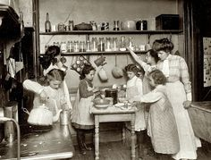 Period Kitchen Photographs - From A Second Course in Homemaking by M.H. Kittredge, 1915: A Canning Lesson.Lots of clear glass jars used for storing foods. Those definitely look like mason jars with screw-on lids. Pots are hung off the bottom-side of the shelf.