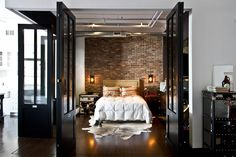 Brick wall as the back drop to the bed, love sconces instead of lamps, love the floor and all the doors that open the room up...