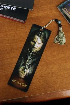 This Aragorn bookmark Features a portrait of Aragorn in his kingly regalia on the front, the Lord of the Rings logo on the back, and a beaded tassel. Laminated plastic bookmark measures 7.25×2.25″ and comes in a clear protective sleeve.