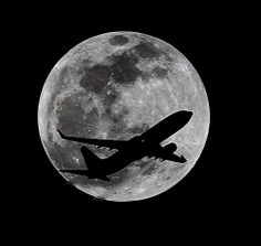 An airliner crosses the moon's path, Monday, April 14, 2014, above Whittier, Calif., approximately one hour before a total lunar eclipse.