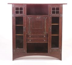 Gustav Stickley 1903.  Fine and rare desk/bookcase designed by Harvey Ellis, with a drop-front desk over two drawers and flanked by two bookcase doors with leaded glass panels, iron hardware, 56 H. x 56 W. x 15 D.