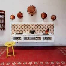 The servants' kitchen, which is no longer in use, has colorful tilework on both the wall and floor. Old copper pots are displayed over a cooking center called a brasero.