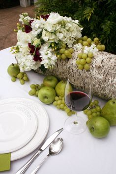 This vintage fruits and flower arrangement is white, green and a touch of hot pink. The challenging part of this project is finding a perfect bark and making a hole without breaking it. The rest is easy just add flowers to the glass vase and decorate the 4 sides of the bark with fruits. As you can see most of my fruits are around the bark and I didn't mix them with flowers just few grapes on top of the bark.    Flowers: hydrangea, stock, lisianthus, hypericum and celosia.  Fruits: apple, grapes, green pear.  Supplies: glass container, bark tree, and scissors  www.ducieldesign.com