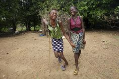 CAN YOU SEE ME? -- Annie Sumo (age 13) laughs while walking home with a friend. Annie contracted a leg infection, during Liberia's civil war, when medical facilities were inaccessible. Untreated, the infection caused a leg deformity. Annie and her friend live in Nyeamah Village, where UNICEF supports a range of services for children. The rebuilding of basic infrastructure has continued since the end of the country's 14-year war in 2003.     © UNICEF/Shehzad Noorani www.unicef.org/photography