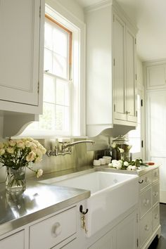 White painted inset kitchen cabinets, stainless steel counter tops, and deep  farm sink (Tim Barber Architecture & Interior Design)
