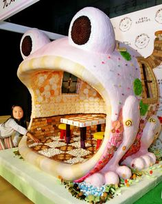 TOKYO: A Japanese girl sits next to a frog-shaped house made of sweets and sugar. More than 120 different kinds of snacks such as chocolate, biscuits, gum and candy were used to decorate the house.