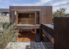 Four red cedar-clad boxes are positioned to form courtyards and gardens in-between the living spaces at this house in a Tokyo suburb.