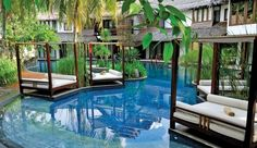 Villa Samadhi, Kuala Lumpur, Malaysia: Four-poster day beds are scattered around the pool lounge for sunbathing and snoozing.