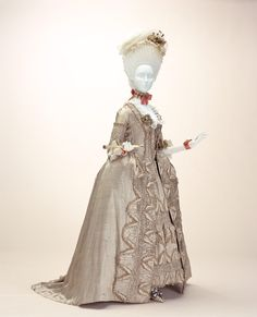 """Dress (""""robe à la française""""), c.1775, France, Beige silk satin with thin stripe and dot pattern; """"compères"""" front; matching petticoat; padded 3-dimensional decoration; trimmed with fly fringe & chenille. Needlework ornaments made with typical French quilting techniques such as """"bouillonné"""", where the cloth is gathered together to create bulk, """"boutis"""", which incorporates cotton padding, and """"tuyauté"""", where the fabric is brought into a tube-like shape, are repeated throughout the garment. KCI"""