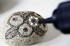 Doodling on rocks with sharpies and white dimensional paint at wise craft